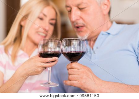 Portrait of a mature couple drinking a glass of red wine