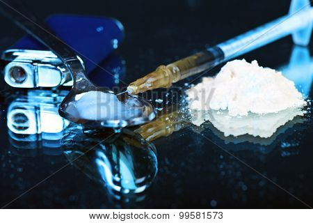 White powder on mirror with lighter spoon and syringe