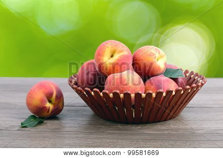 Ripe peaches at basket on table over green