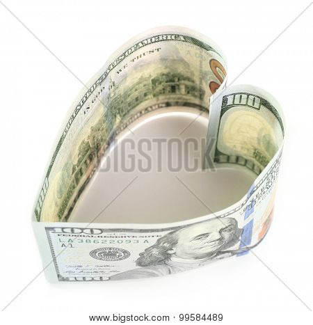 Dollars folded into heart isolated on white