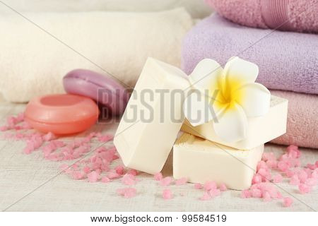 Bars of natural soap and colorful towels on light background
