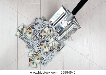 Shovel lifts dollar bills on floor