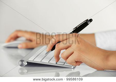Female hands holding pen and computer mouse on light background
