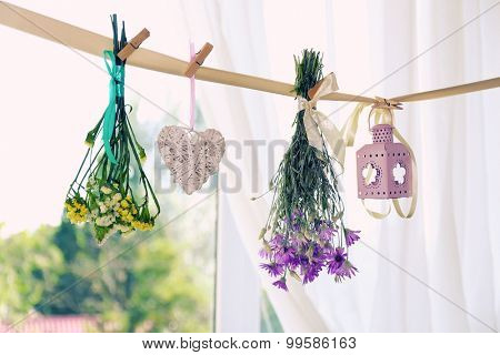 Various herbs, flowers and decorations hanging on thong on light background