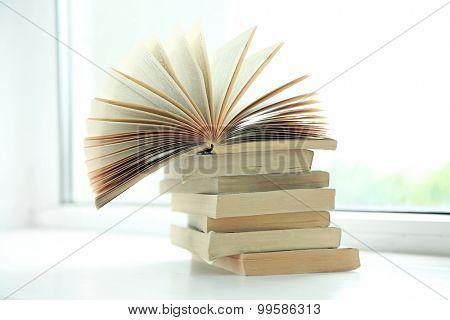 Books on white windowsill, close up