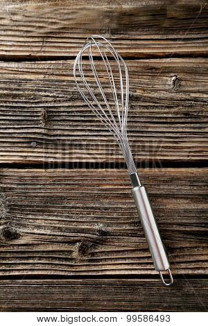 Stainless Steel Egg Whisk On Brown Wooden Background