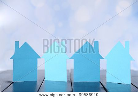 Paper houses on bright background