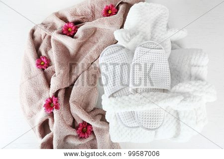 Bath set with white bathrobe, towel and slippers, top view