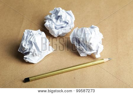 Crumpled paper balls on brown background