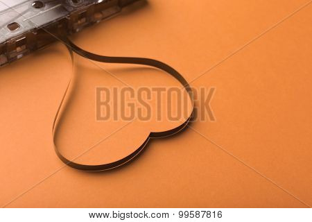 Audio cassette with magnetic tape in shape of heart on orange background