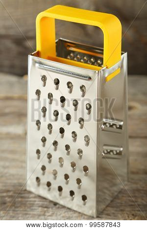 Metal Grater On Grey Wooden Background