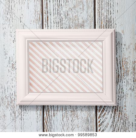 White frame with striped canvas on wooden background