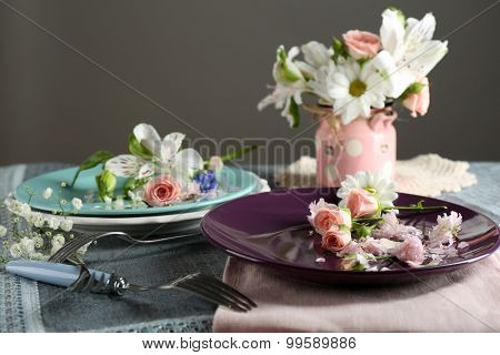 Tableware with flowers on table on gray background
