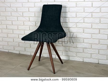 Modern chair on brick wall background