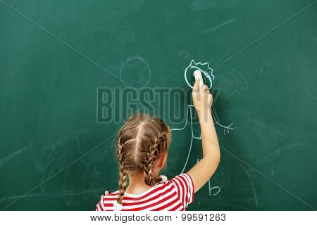 Girl drawing on blackboard, close-up
