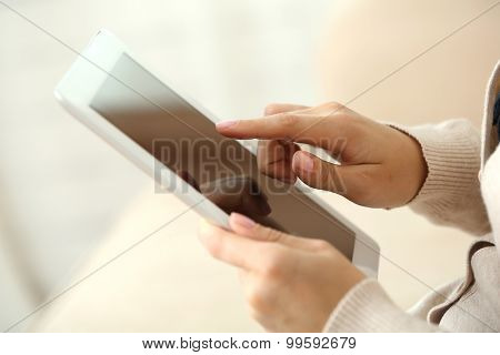 Female hand holding PC tablet on home interior background
