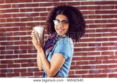 Portrait of smiling attractive hipster holding take-away cup against red brick background
