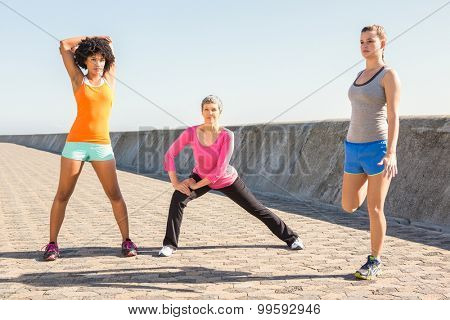 Sporty women stretching together at promenade