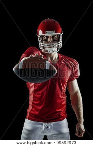 American football player showing ball on black background