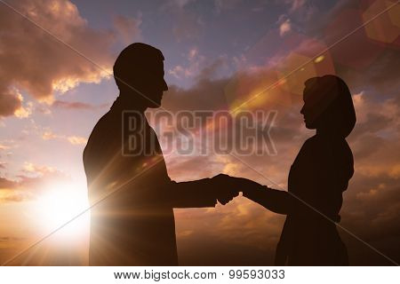 Silhouette of business people shaking hands against sun shining