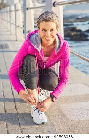 Portrait of smiling sporty woman tying her shoelace at promenade on a sunny day