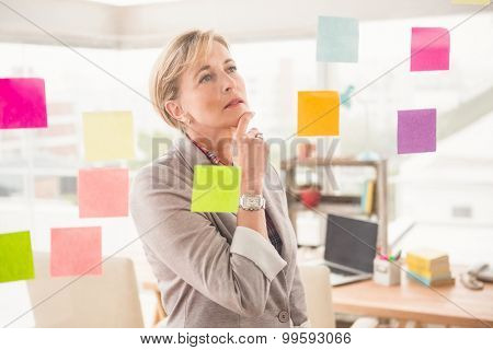 Casual businesswoman reading sticky notes in the office