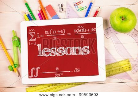 The word lessons and maths equation against students desk with tablet pc