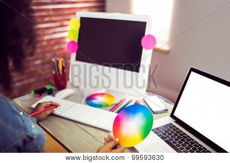 Casual female designer working with computer against red brick background