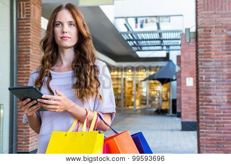 Pretty woman shopping at the mall using tablet on a sunny day