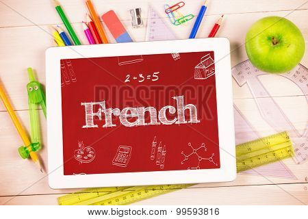 The word french and school doodles against students desk with tablet pc