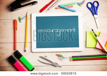 The word encouragement and students desk with tablet pc against teal, blue