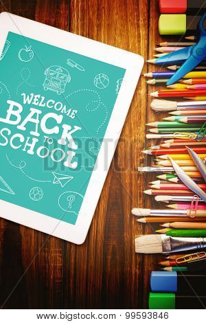 Back to school written on chalkboard against students desk with tablet pc