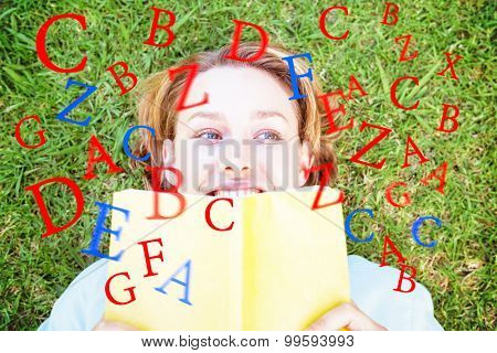 letters against pretty woman reading book in park