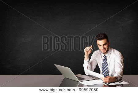Business man sitting at black table with a laptop on black background