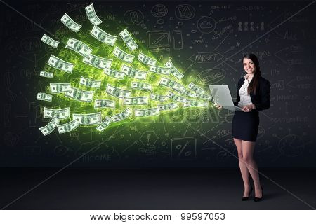 Businesswoman sitting in chair holding laptop with dollar bills coming out concept on background