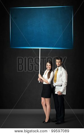 Young business couple holding a big, blue board