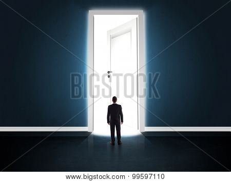 Business man looking at big bright opened door concept