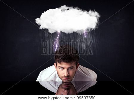 Depressed businessman sitting under a lightning rainy cloud
