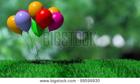Group of colorful balloons on green grass and abstract background
