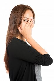 picture of shy woman  - Profile of playful Asian woman in casual clothes dress sweatert covering face with hand eye peeking through split finger showing shy curious fearful emotions - JPG