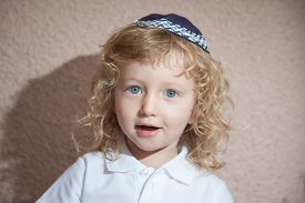 foto of sukkot  - The charming little boy with blue eyes and long blond curls in Jewish knitted skullcap - JPG
