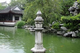 foto of tong  - A stone pillar in the water with an orange carp swimming around it in the gardens of Tongli Pearl Pagoda - JPG