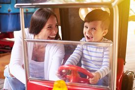 stock photo of merry-go-round  - excited woman with little boy driving a car on merry - JPG