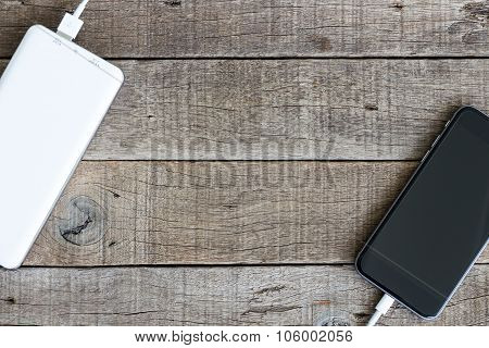 Phone Charging With Power Bank On Wood Background