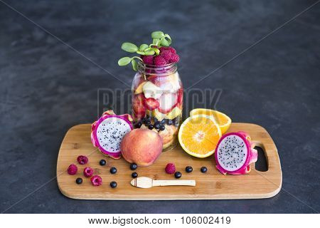 Mason jar full with tropical fruits, topped with sunflower sprouts in a blue and wooden rustic surface