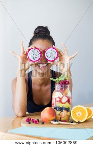 Woman smiling with a tropical fruit salad, being playful attitude covering her eyes with pitahayas.