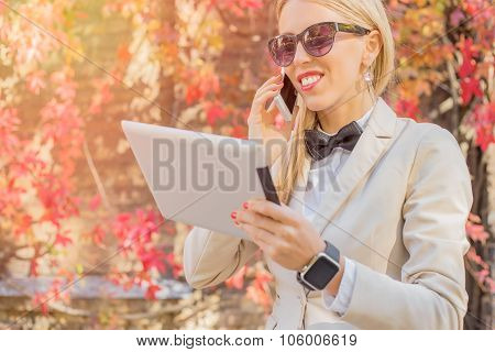 Female talking on the cellphone and looking at tablet