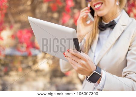 Woman on the phone with tablet in her hand