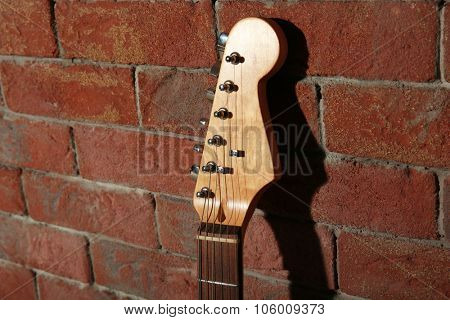Guitar's fingerboard on brick wall background
