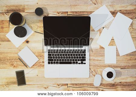 Blank Desktop Of Laptop, Papers, Diary And Coffee Mug On The Wooden Table